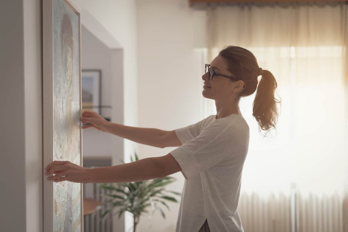 Woman with blonde hair and glasses hanging a piece of art on the wall