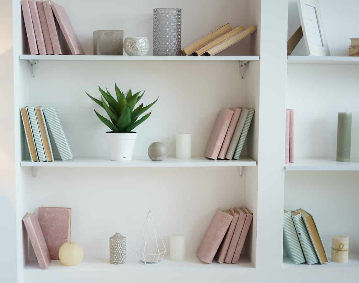 White bookshelves with blue and pink books and knick-knacks.