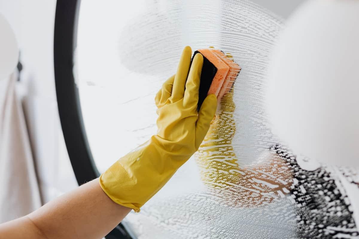 Hand in a yellow glove scrubbing a circular mirror clean