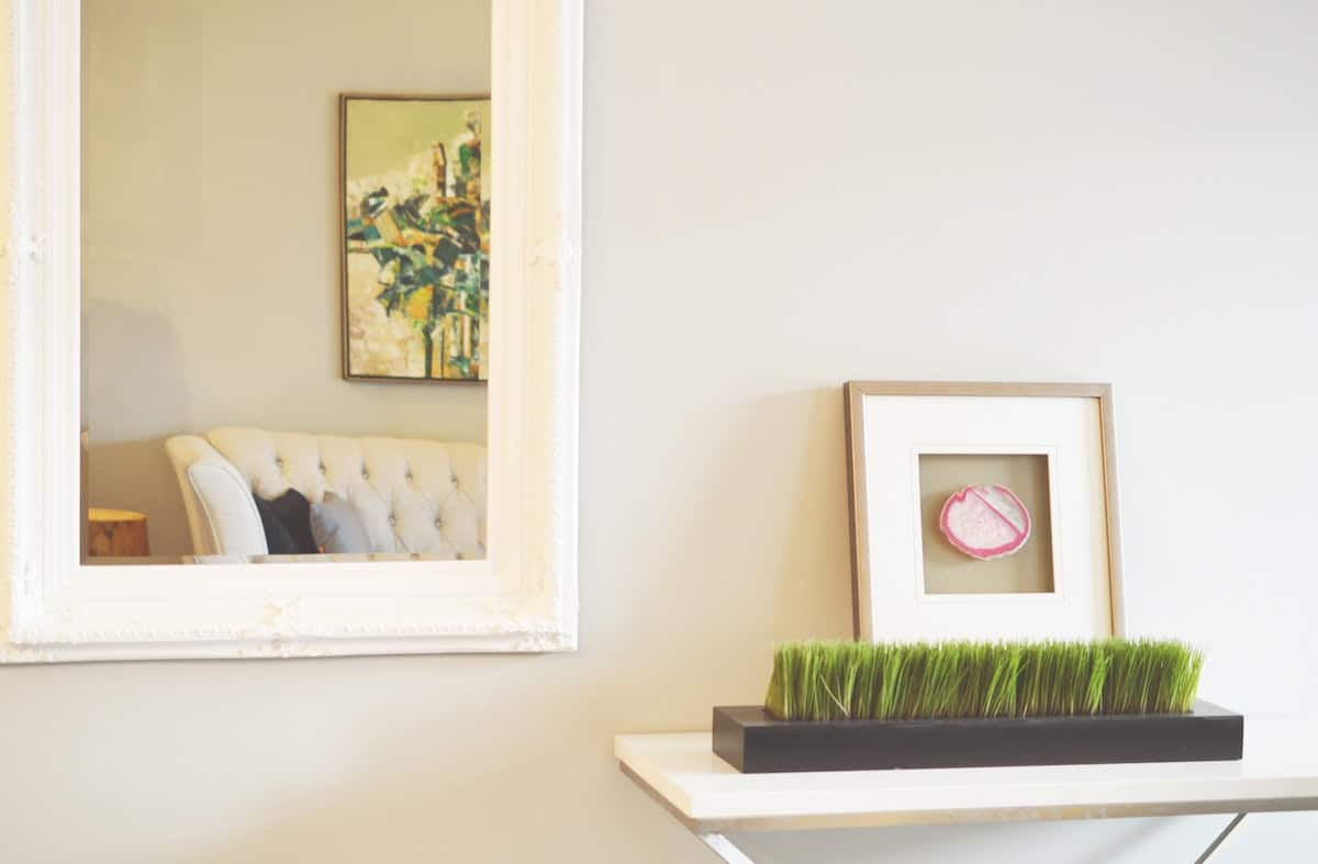Interior decoration of an apartment with a mirror and box of fake grass next to art and a white wall