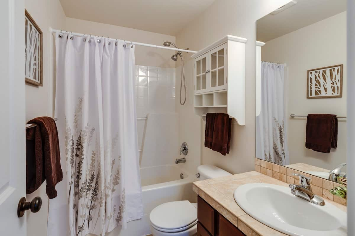 Bathroom with brown and white interior accents, looking into the shower.