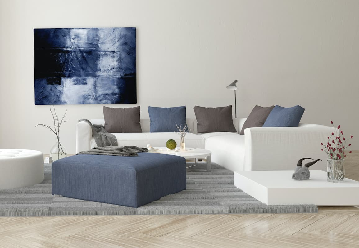 White couch on a grey rug next to a blue ottomon and a blue canvas.