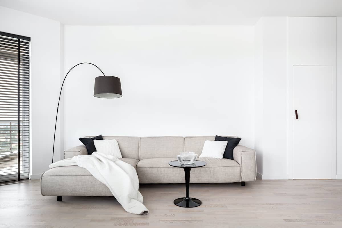 Tan living room couch against a white wall next to black blinds and a lamp.