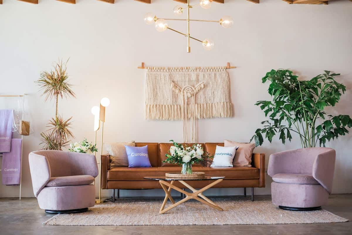 Living room with bright lights, pastels, a tan couch and a macrame wall hanging next to a plant boho decorating