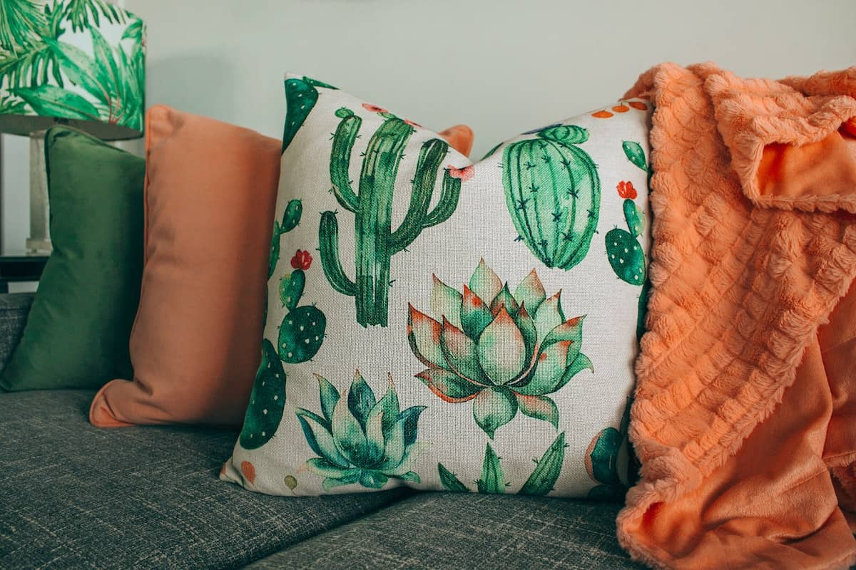 Funky and fun pillows on a gray cough, one pillow is covered in cactus plants.