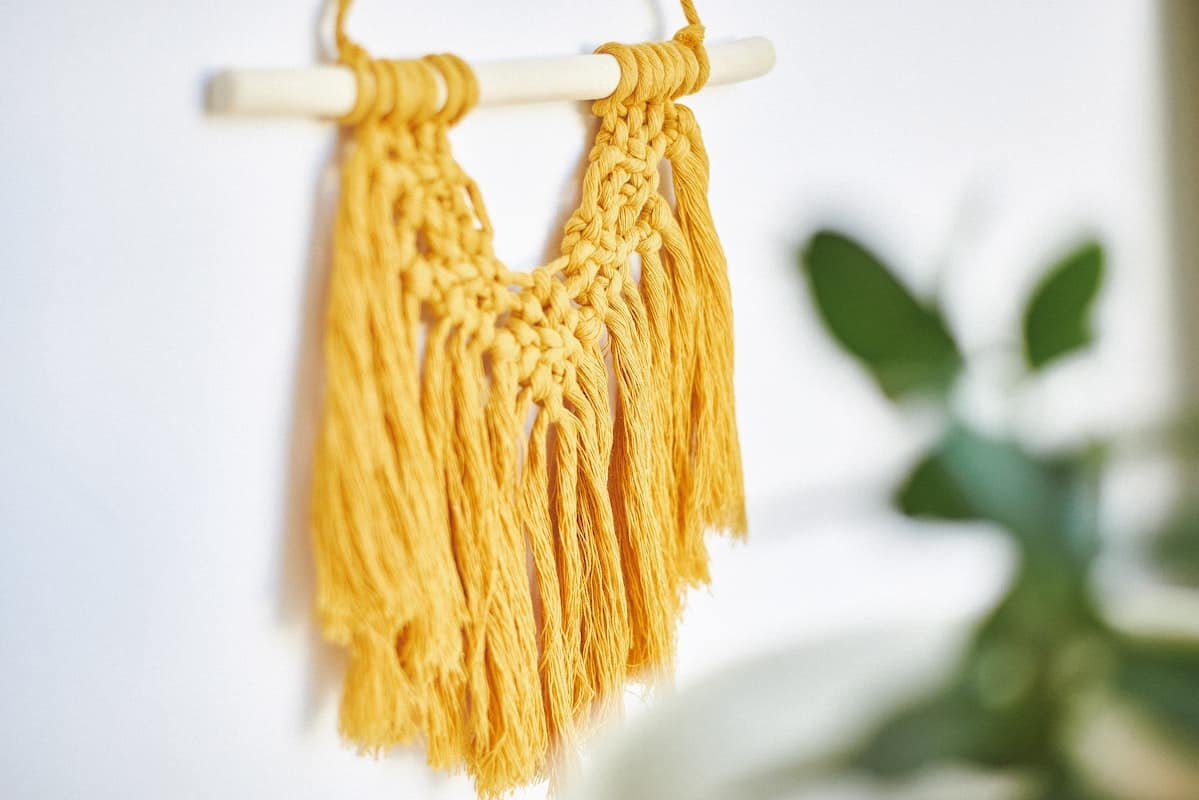 A yellow macrame wall hanging is displayed on a wall boho decorating
