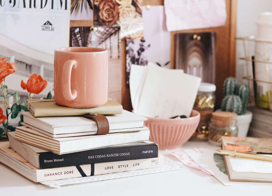 Stack of books with a pink coffee cup on top boho decorating