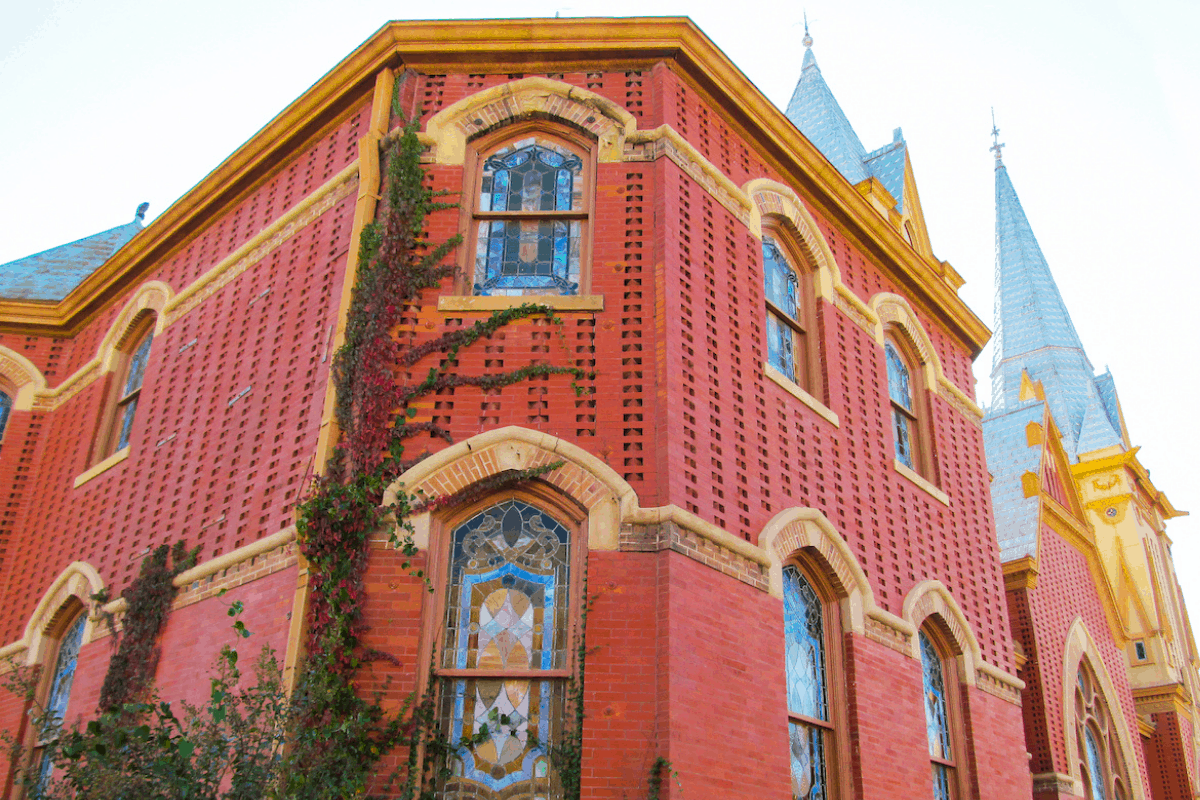 An old church building with ivy growing on it. The building is red with stained glass windows.