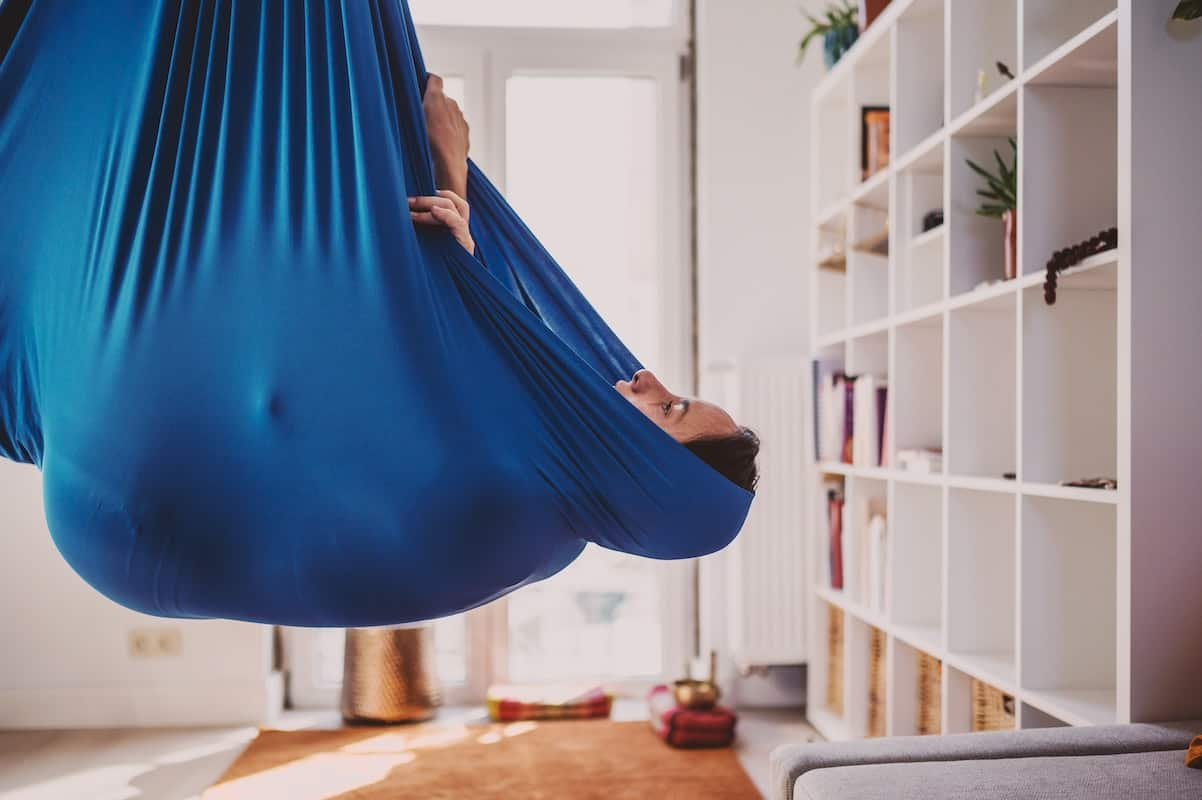 Person hanging in a blue indoor hammock next to a white bookcase.