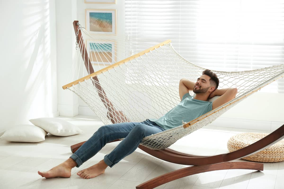 Man with a dark beard sitting in a hammock indoors.
