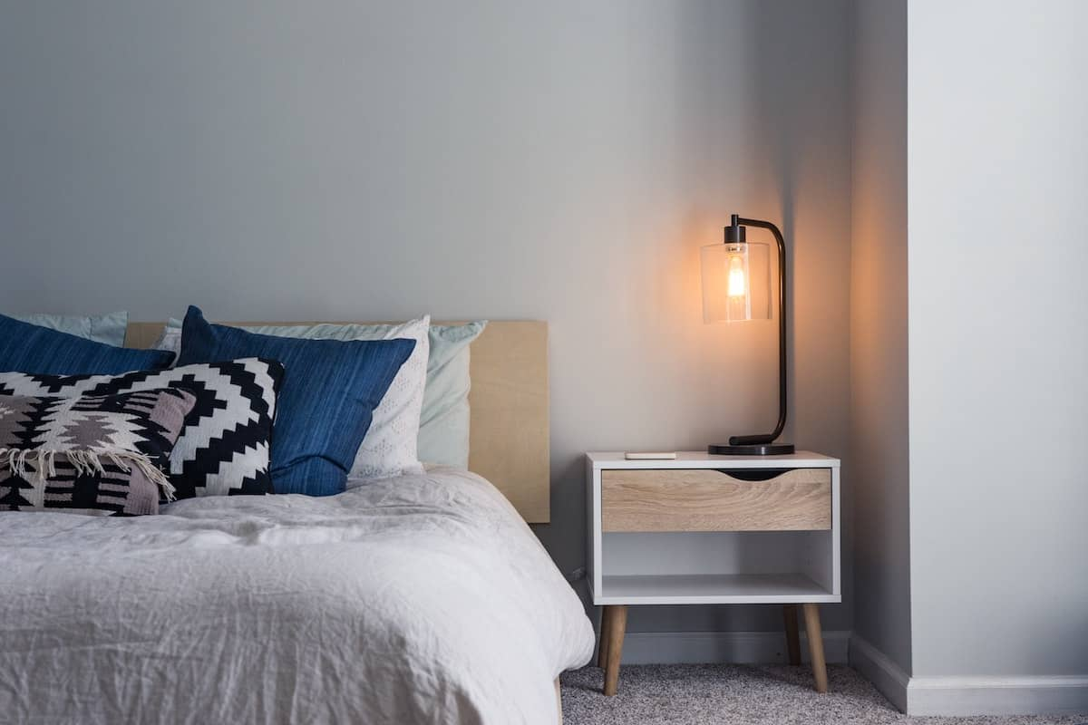 Bed with a grey comforter next to a wooden night stand with a lamp on. small bedroom ideas