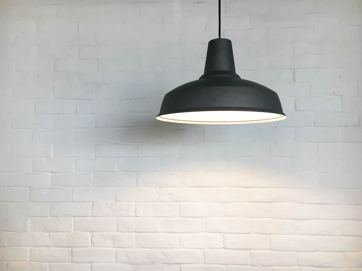 White brick wall with a black light fixture next to it small living room ideas