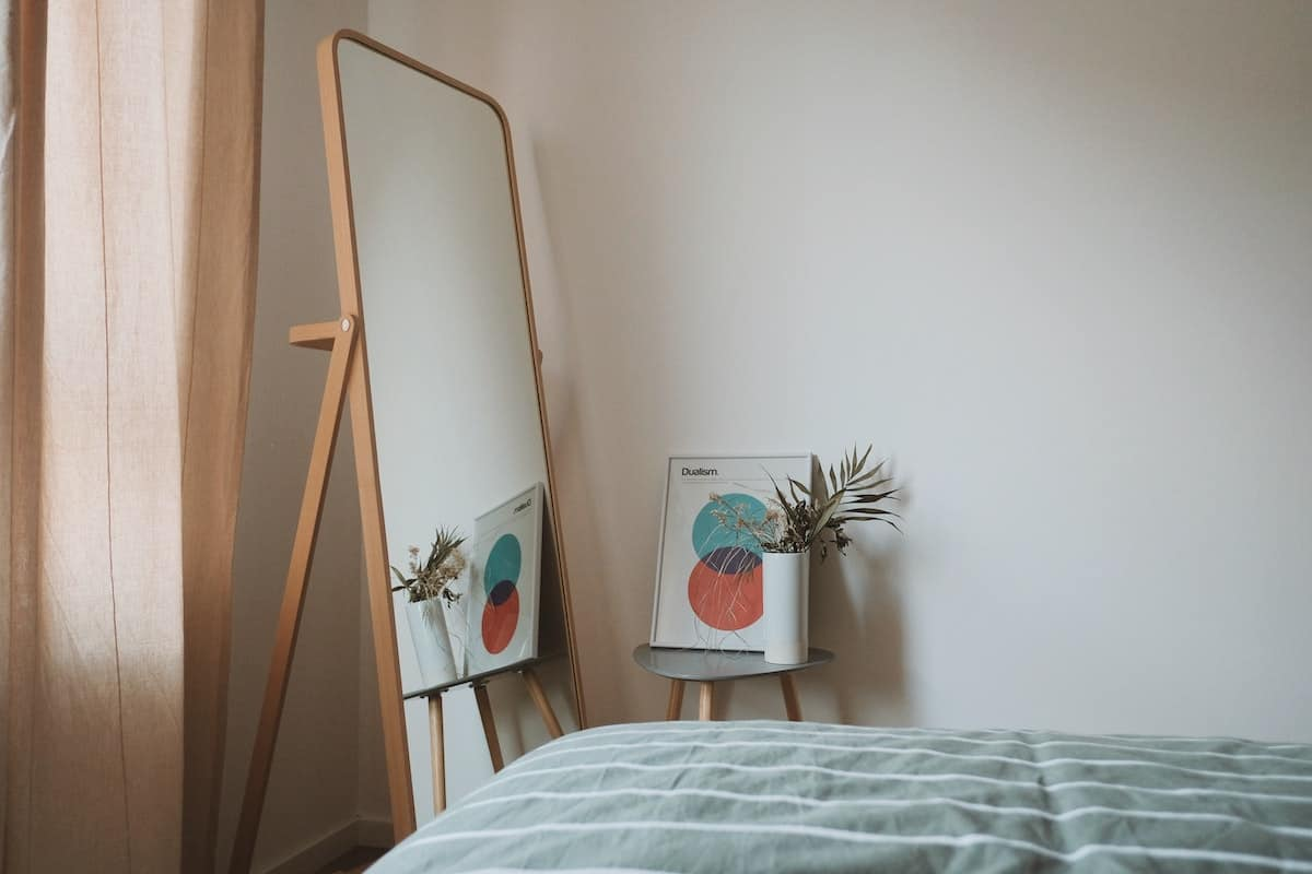 Light blue comforter on a bed next to a side table with a plant and piece of art on it, next to a stand up mirror.