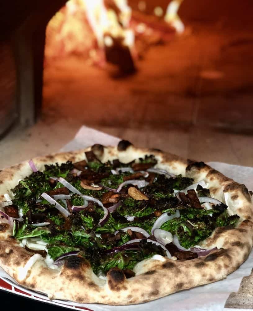 A woodfired pizza topped with kale and red onions vegan restaurants portland
