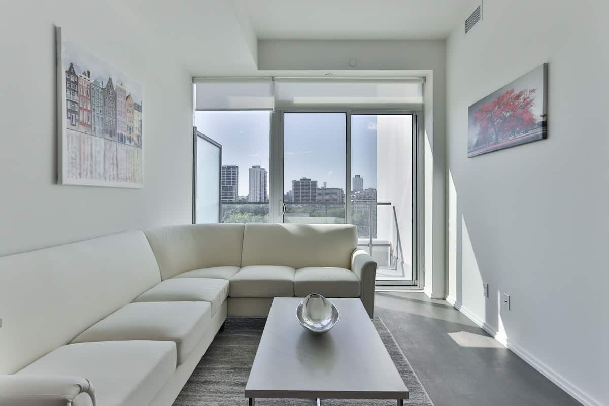 Long white couch in a penthouse apartment with art and a TV on the walls with an outside deck that looks towards a city skyline.
