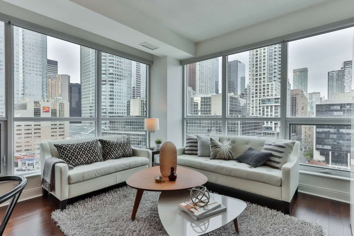 Penthouse apartment with modern decor in shades of gray and brown with a city in the background.