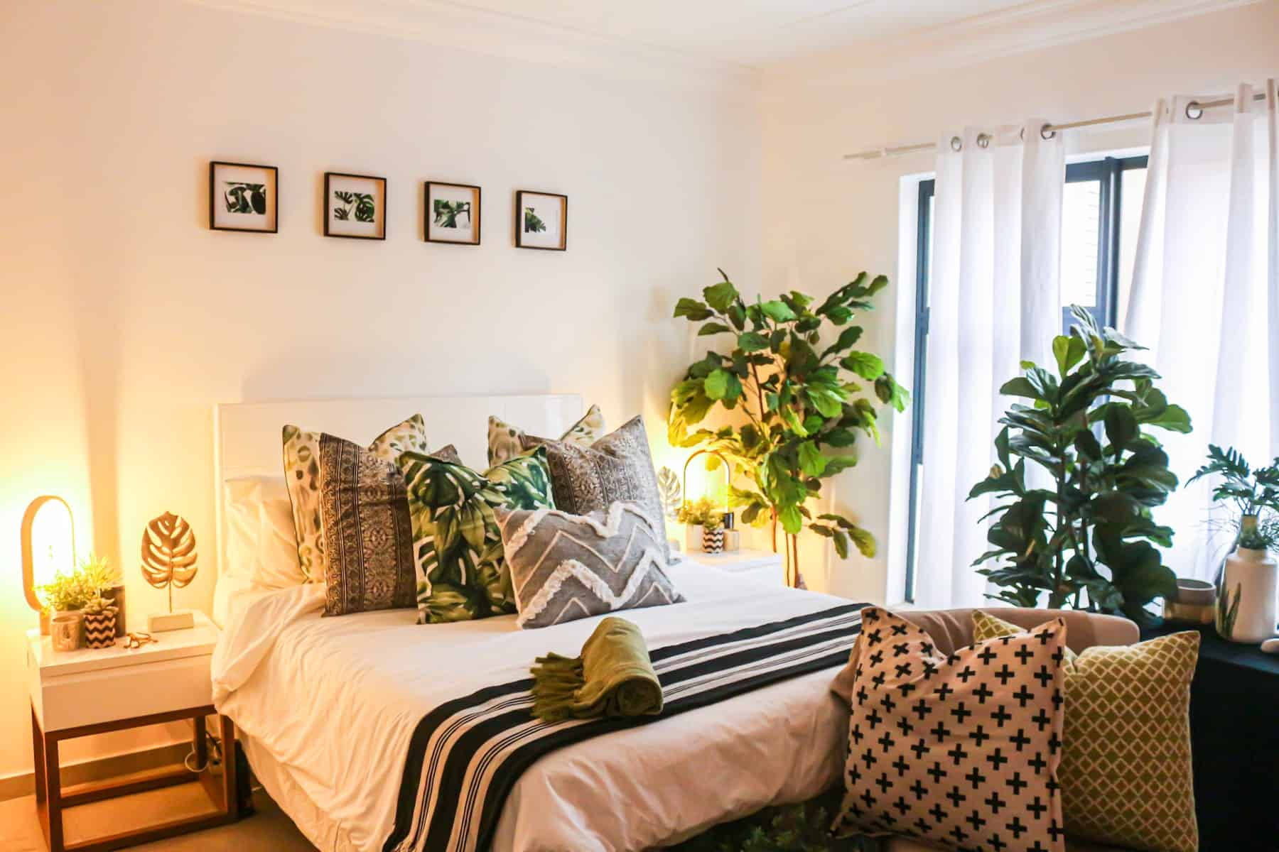 A bedroom with many plants inside of it around the bed.