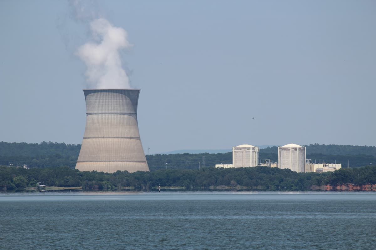 Large body of water next to a power plant releasing smoke into the air, surrounded by green trees and blue skies.