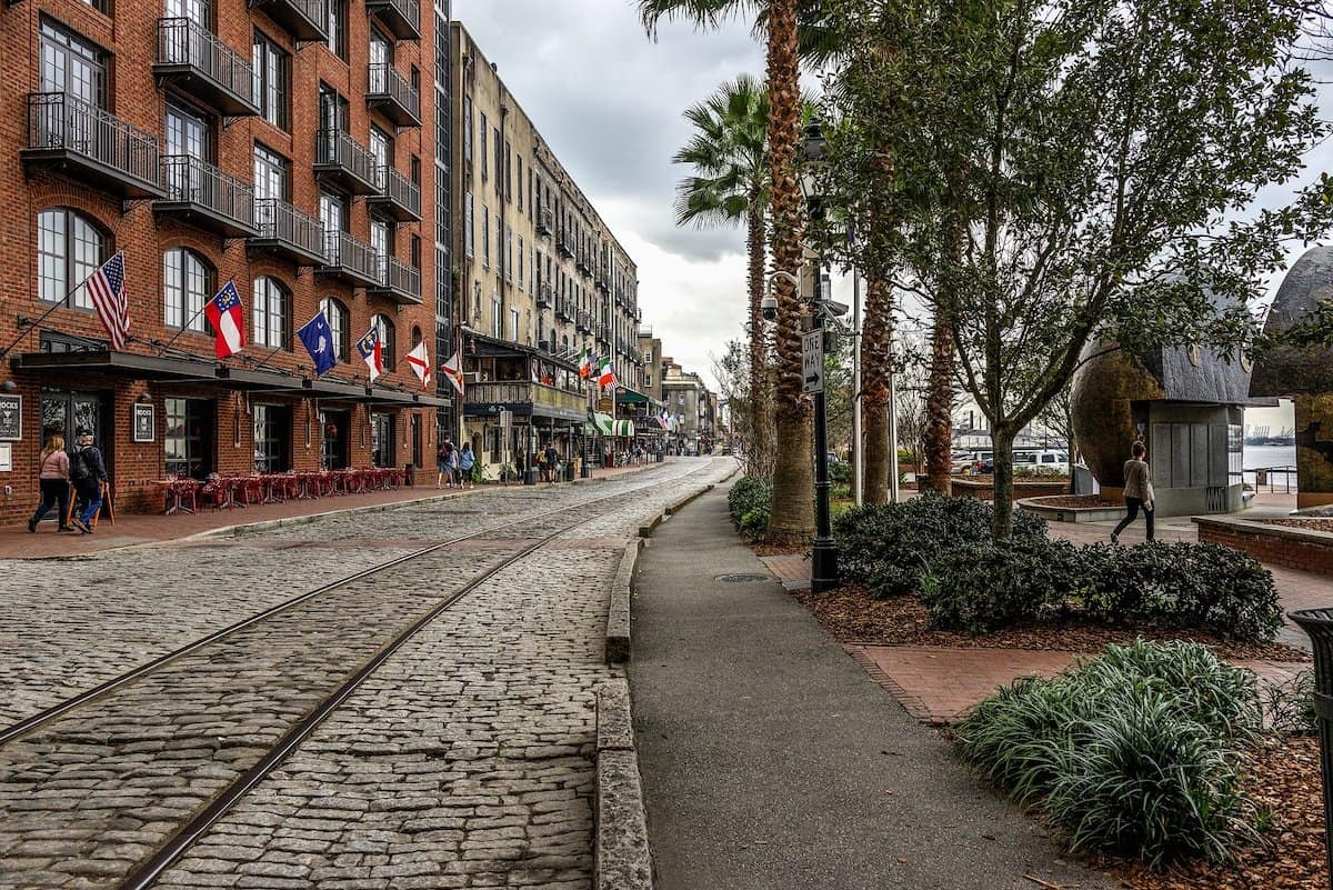 Cobblestone street in Savannah with flags lining the buildings on the left.