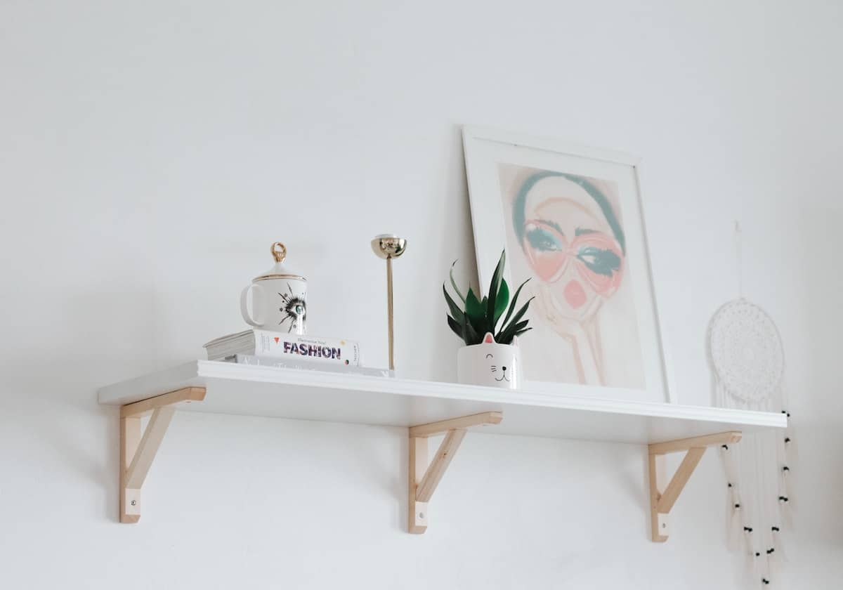 A white shelf on a white wall with white knick-knacks on it. small bedroom ideas