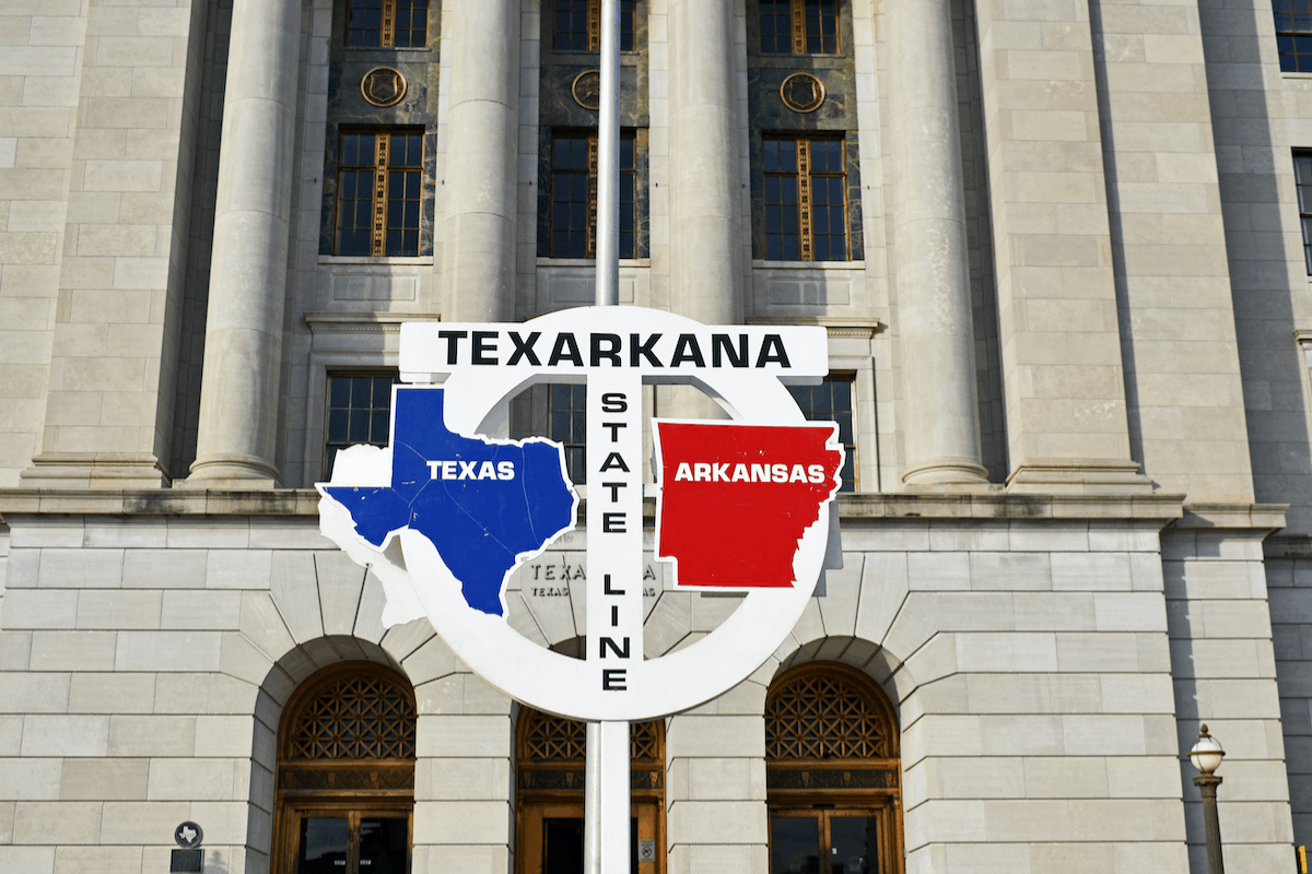 A sign marking the state line of Texas and Arkansas.
