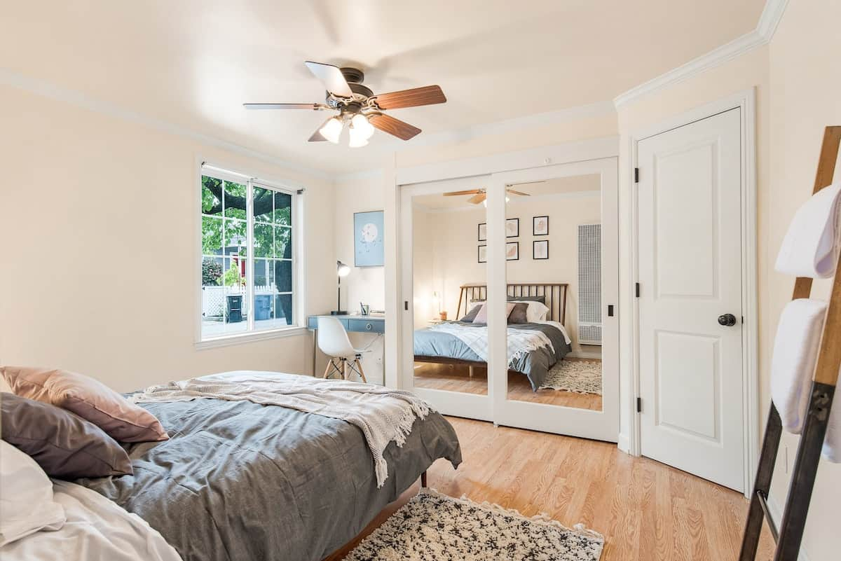 Bed with a light blue comforter facing a window and a mirror with an overhead light fan on.