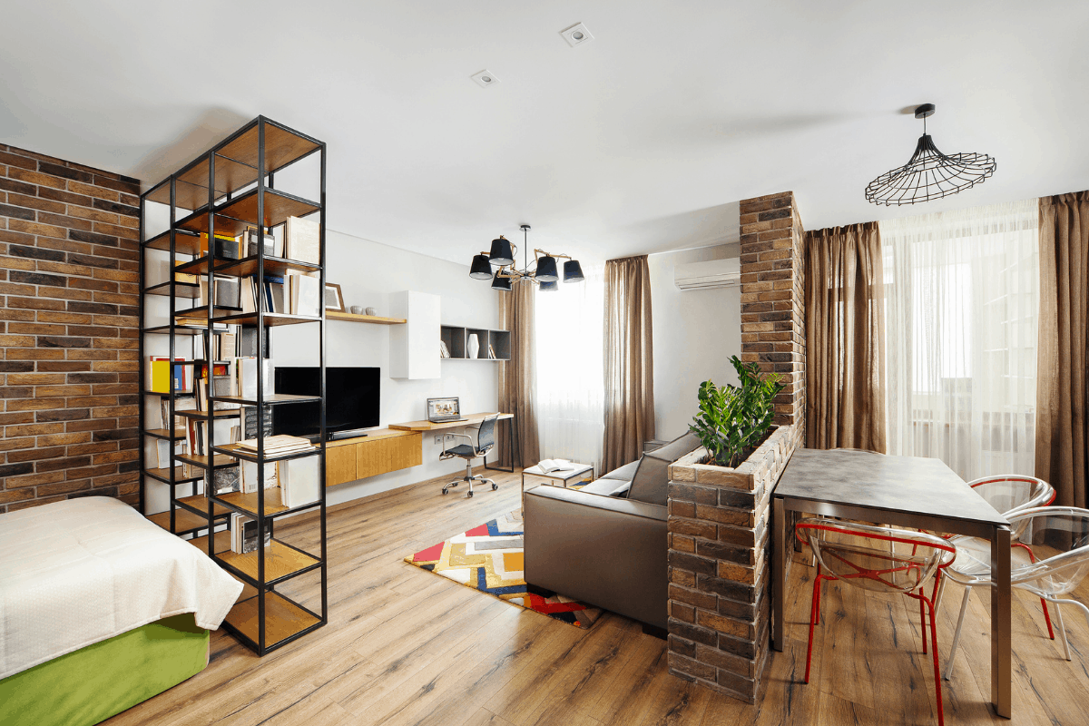 A studio apartment with a bookshelf, bed, couch and kitchen table.