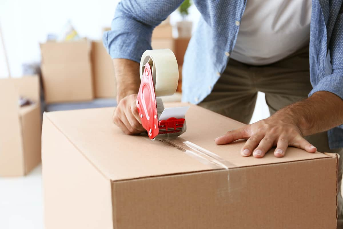 A man taping up a box in preparation for moving.