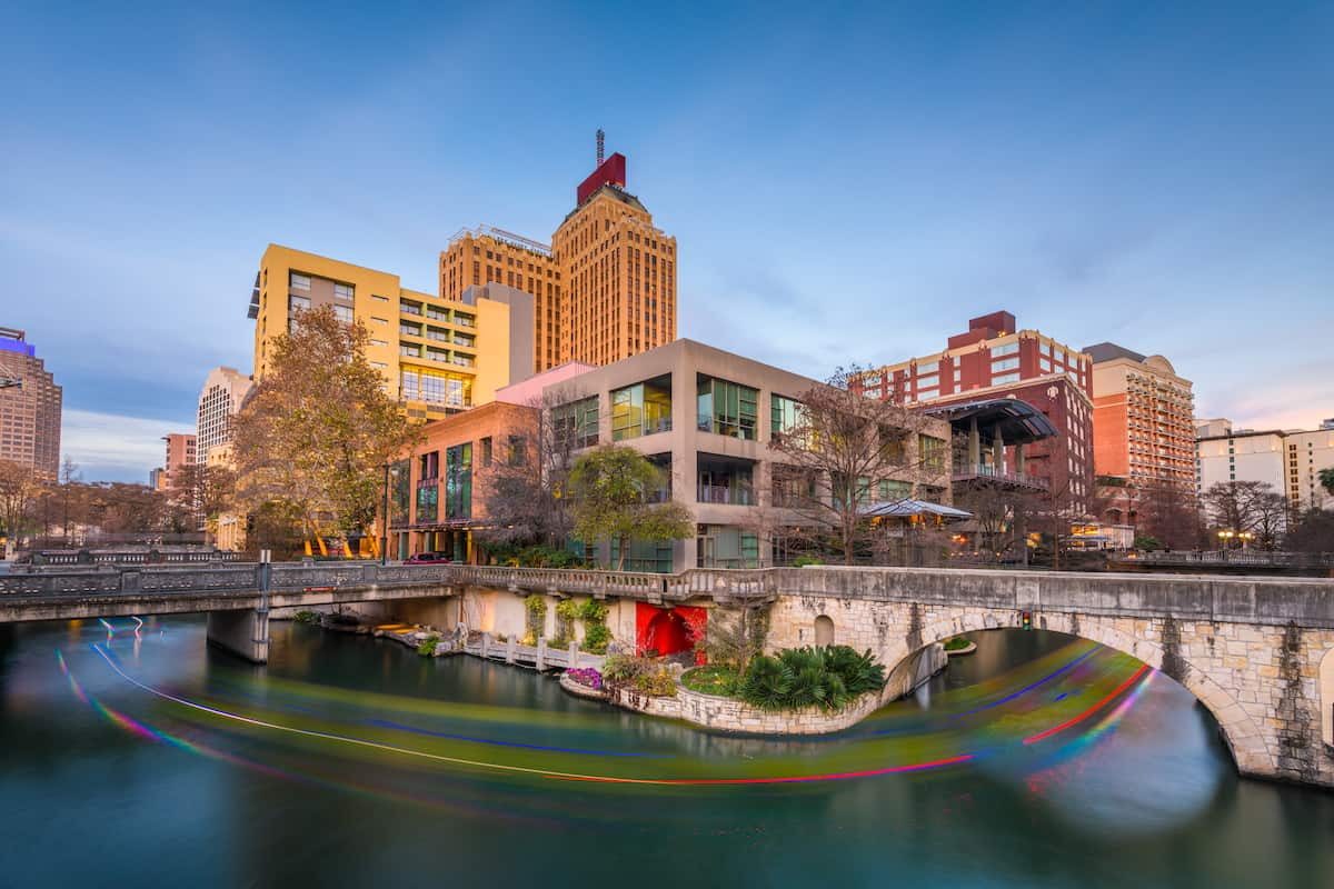 River running through San Antonio with buildings around it and a blue sky.