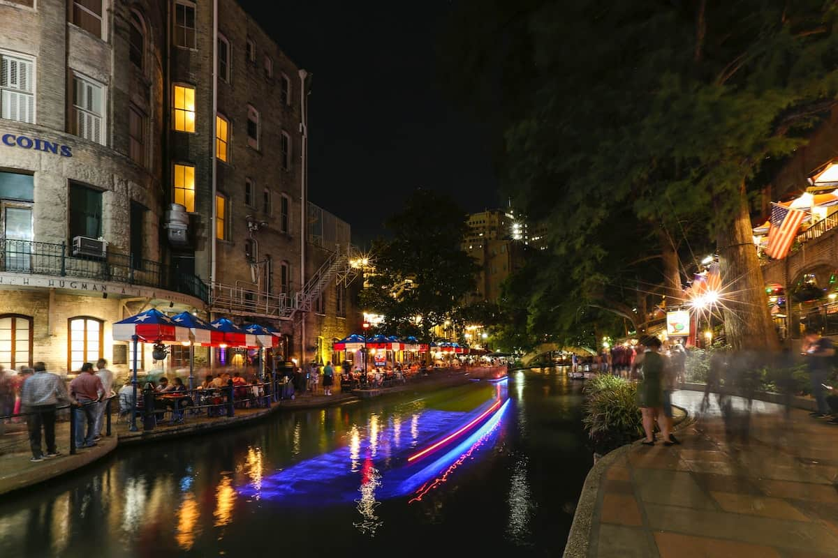 The San Antonio River Walk with people strolling on both sides of the river outside of restaurants and shops at night.