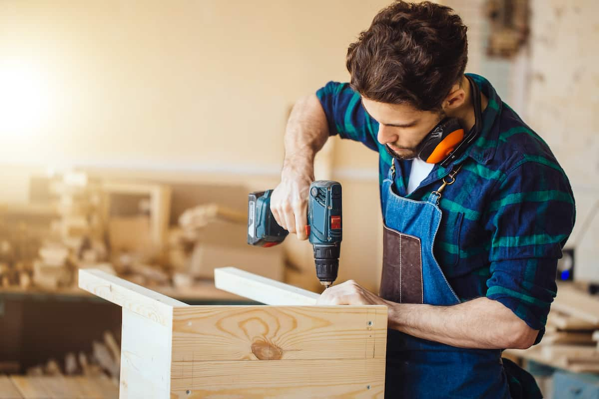 A white man using a drill on a piece of furniture