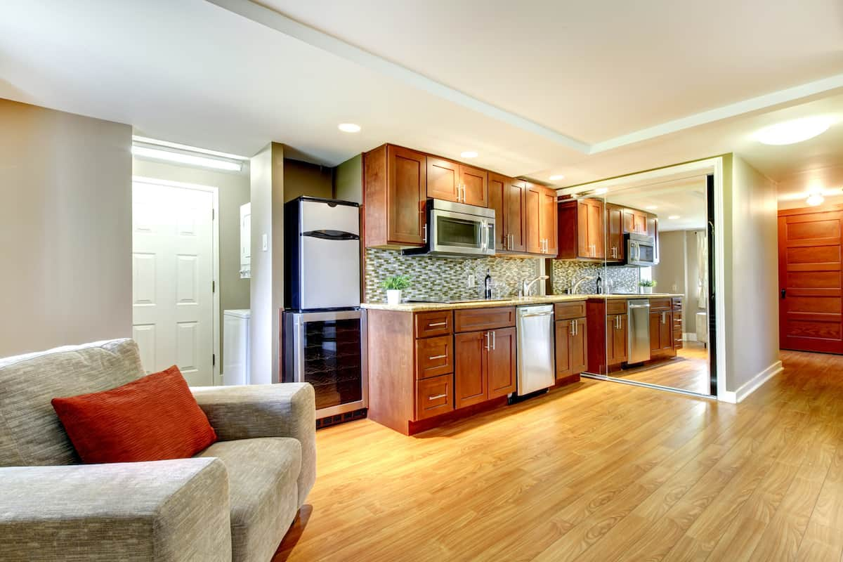 Living space with hardwood floors, an oversized chair and appliances.