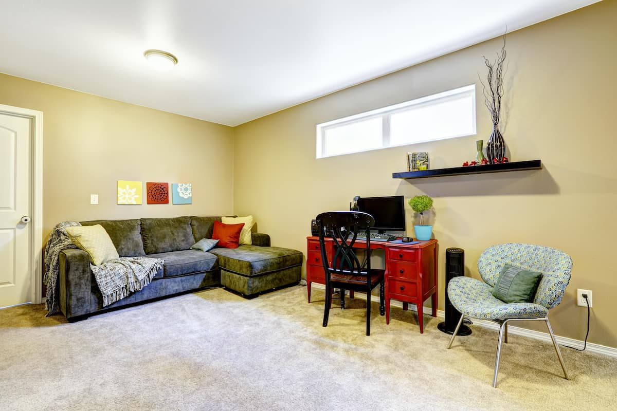 A basement apartment with carpet, a couch, a desk a chair and a window.