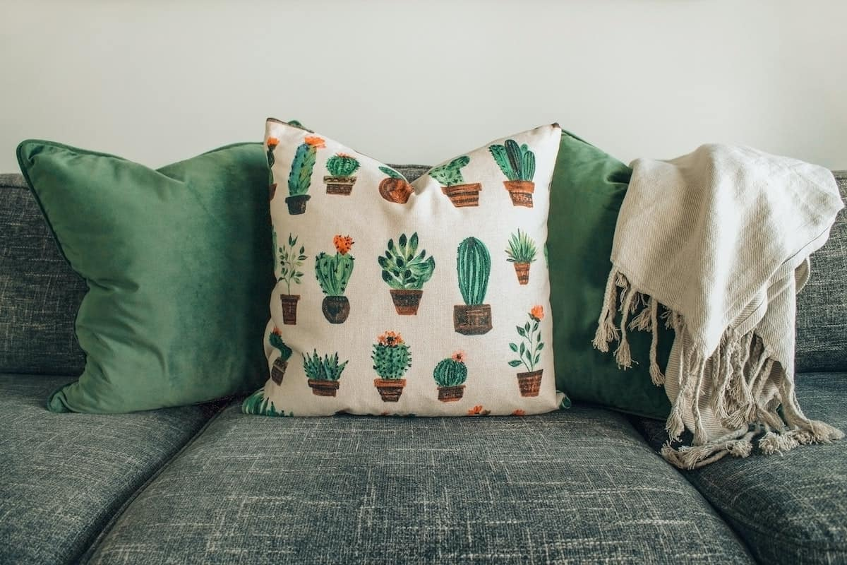 A throw blanket on a couch and pillows