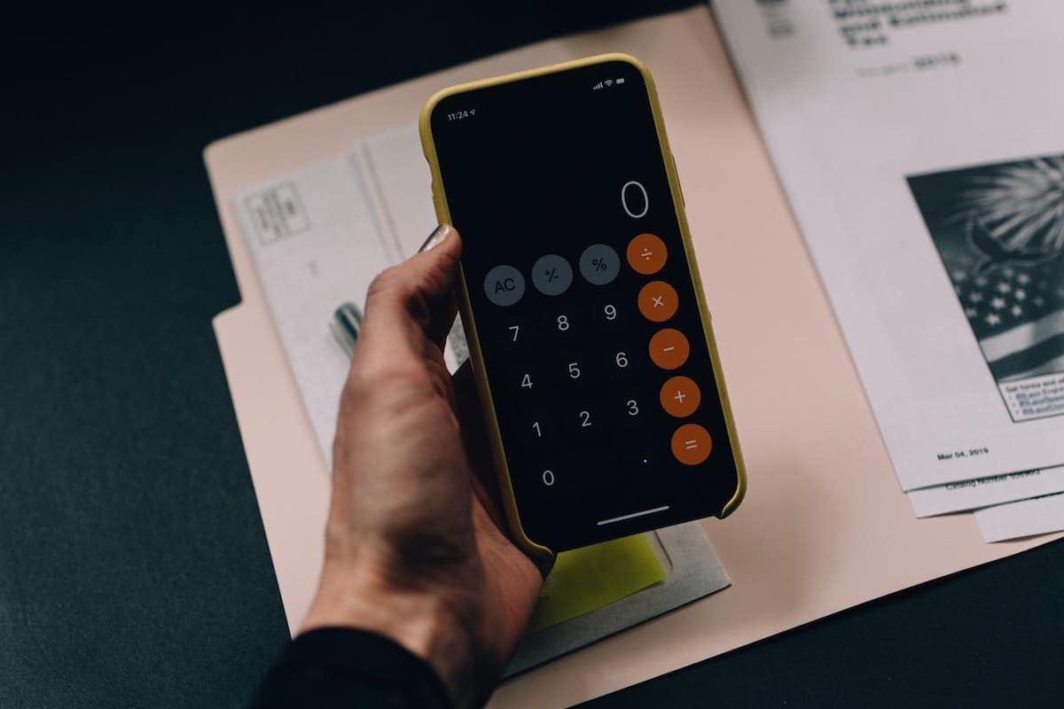 Phone with a calculator open and paperwork next to it.