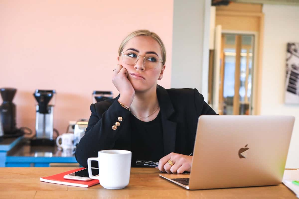 Blonde woman looking upset at her laptop next to a coffee cup.