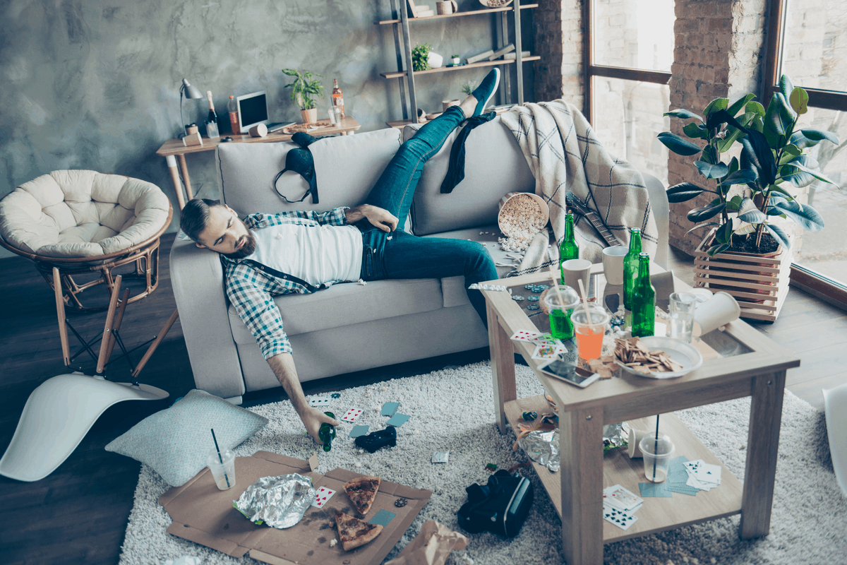 Messy apartment with a man on a couch.