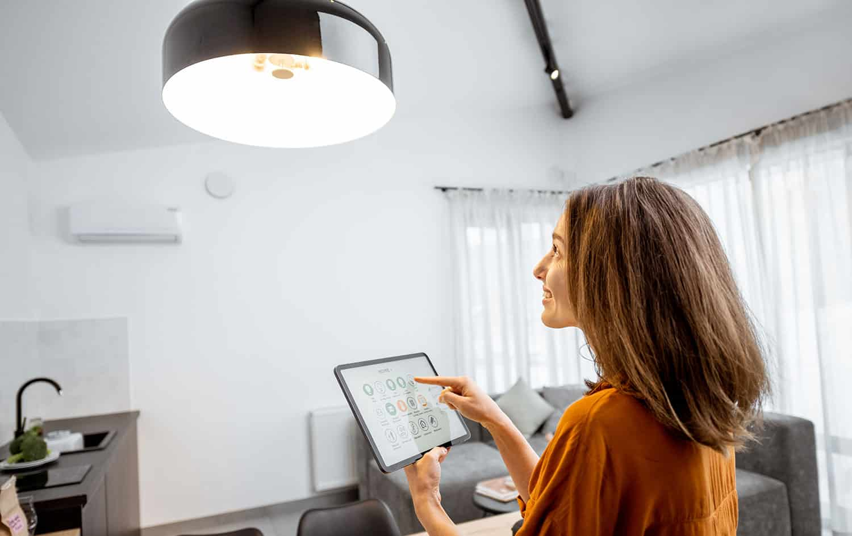 Woman turning on light with ipad