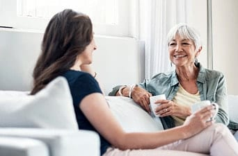 Shot of an elderly woman and her daughter having a chat over coffee on the sofa at home